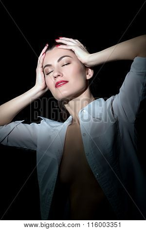 Sexy girl in blouse posing while holding her head