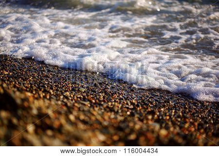 Coastline, waves and coastal pebbles at sunset