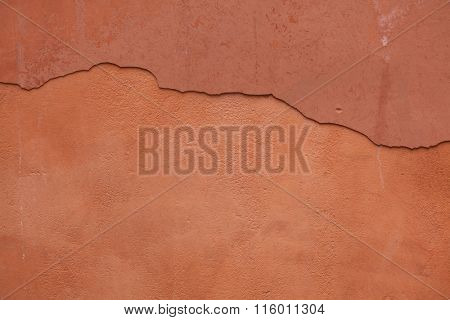 Old terracotta painted stucco wall with cracked plaster. Background texture.