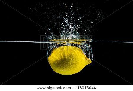 Yellow lemon splashing in water