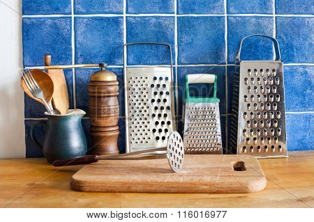 Kitchen still life. Vintage utensils. kitchenware graters, ceramic jug, spoons. cutting board. Blue