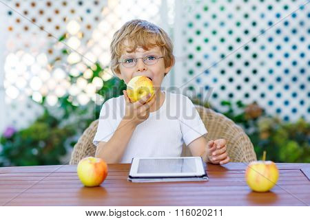 kid boy with glasses playing with tablet and eating apple