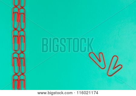 Green Background With Red Clips. Two Red Paper Clips Form Heart