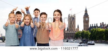 happy children showing thumbs up over london