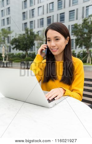 Young Woman talk to cellphone and use of the laptop computer