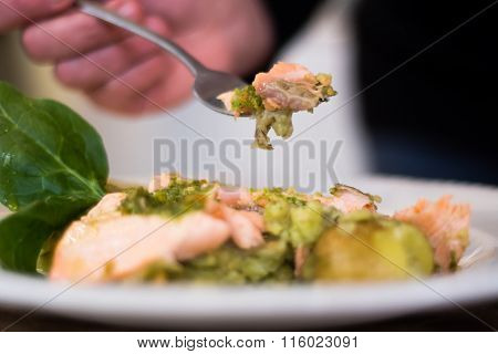Salmon fillet, pesto and crushed potato on fork