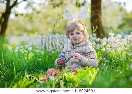 Cute happy little boy wearing Easter bunny ears at spring green