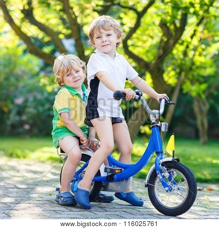 Two little kid boys riding with bicycle together