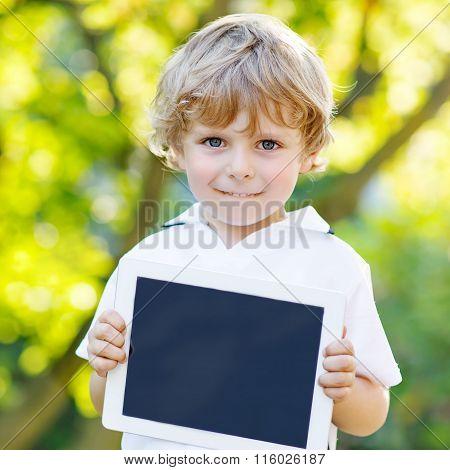 Preschool little boy with tablet pc, outdoors