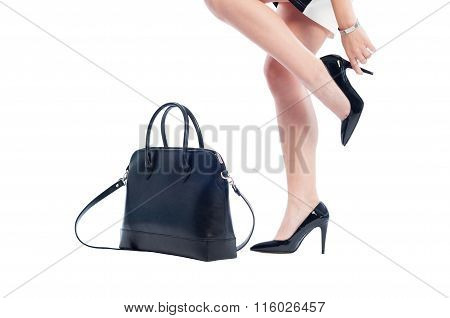 Business Woman Legs With Black Shoes And Leather Handbag.