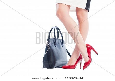 Woman Legs, Red Shoes And Black Handbag Or Purse.
