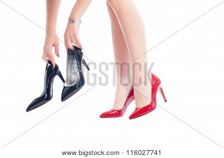 Woman Wearing Red Shoes Holding Black Shoes.