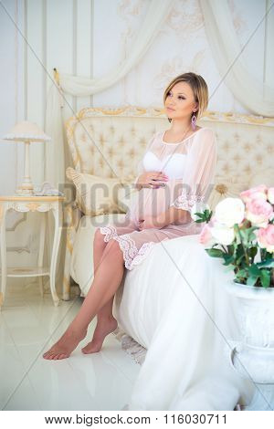 Beautiful Pregnant Girl In A Home Clothes Sitting In The Interior On A Bed Of Roses