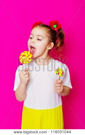 Little girl in a beautiful dress with a big candy lollipop