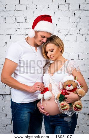 Young Pregnant Family With A New Year Santa Hat And Christmas Teddy Bear. Happy Pregnancy
