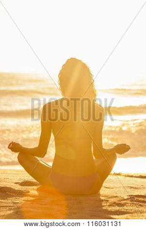 A relaxed sexy young brunette woman or girl wearing a bikini sitting on a deserted tropical beach at sunset or sunrise