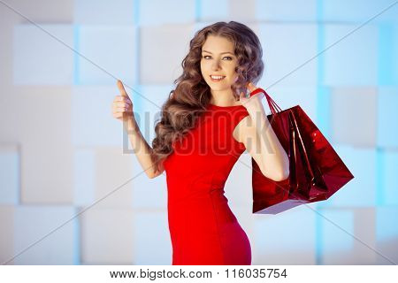 Shopping woman with red bags, presents in mall. shopping center. Girl shopper. Sale, discount in supermarket. Black friday, cyber monday sales