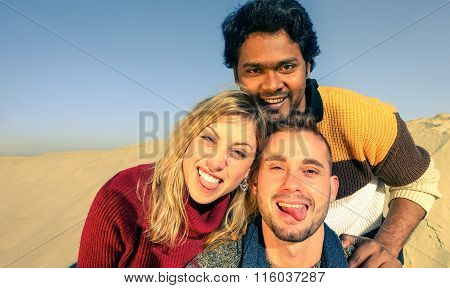 Group Of Multiracial Best Friends Having Fun Taking Selfie With Smartphone On The Desert Dunes