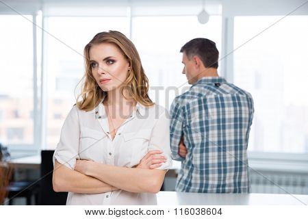 Unhappy woman standing with arms crossed in quarrel with her husband at home