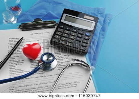 Medical stethoscope, clipboard, coat and calculator on blue background