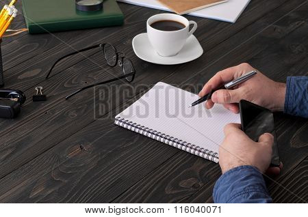 Man Writes In A Pad On A Wooden Table