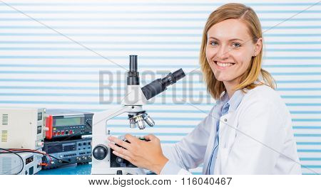 Young woman witch blonde long hair testing blood on RBC, HGB and HCT. laboratory bench which blood sample and microscope