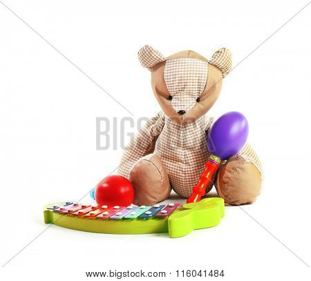 Teddy bear with maracas and xylophone, isolated on white