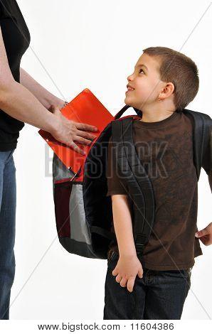 Happy boy preparing for school with mom's help