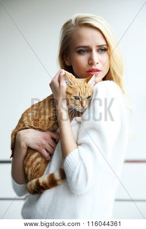 Young woman holds red cat in hands, close up