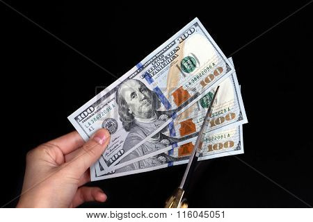 Hands with scissors cutting dollar banknotes, on black background