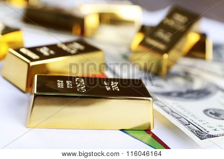 Gold bars with dollar banknote on paper background