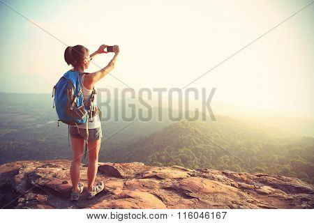 young woman hiker use cellphone  taking photo on mountian peak
