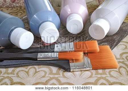Four bottles with acrylic paint and brushes for handmade, hobby and decoration
