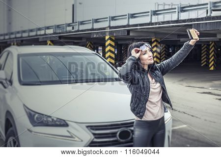 Beautiful Sexy Female Model With A White Car And A Smartphone Makes Selfies