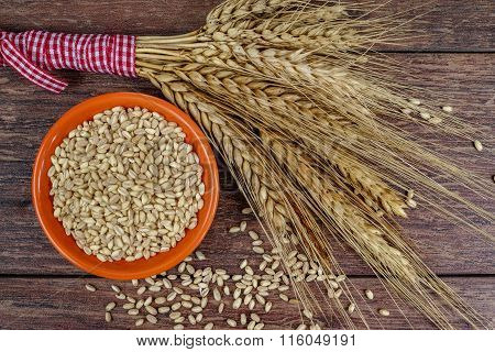 Bowl with whole wheat and sheaf of wheat ears
