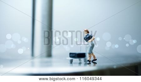 Miniature people -  A woman pushes a cart with luggage