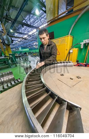 Worker assembles part for aviation engine