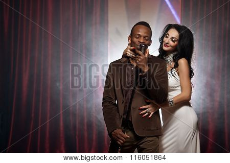 White Woman And Black Man Singing Into A Microphone At The Bar, Couple Singing