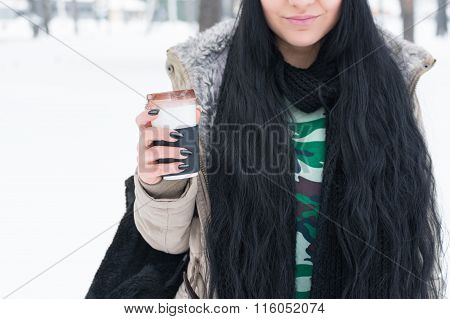 Young woman in winter holding a cup of takeaway coffee