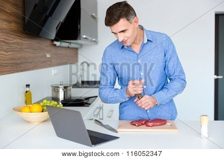 Handsome male in blue shirt watching cooking lesson on laptop and preparing meat on the kitchen