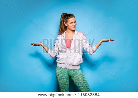 Young Athletic Woman In Hoodie On Blue Background