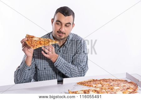 Young man eating pizza with cheese on a white background