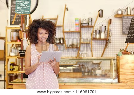 Small business owner using a tablet in her coffee shop