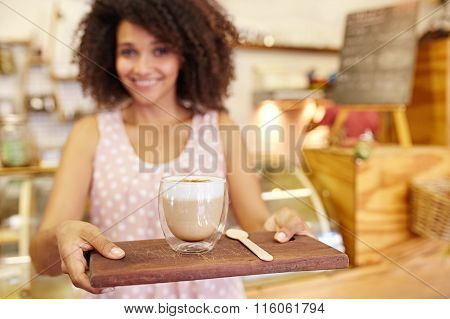 Latte on a wooden tray being carried by young waitress