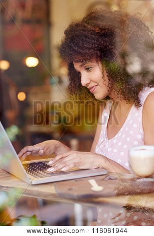 Young woman working on her laptop in a coffee shop