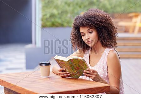 Beautiful woman reading a book outside with takeaway coffee