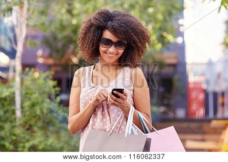 Smiling woman using her phone outdoors while shopping