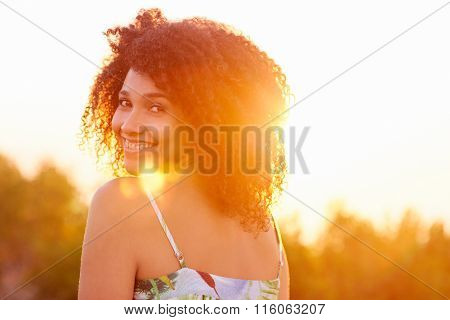 Woman looking back over her shoulder with sun flare