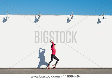 Woman riding roller skates skating and holding her hands up. Young woman practicing rollerskating against white wall with arm stretched upwards. Happy girl with rollerskates in the skating ground.