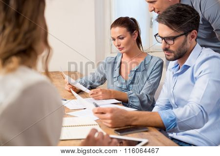 Businesspeople meeting in a boardroom. Business team using reports in a meeting. Brainstorming of business teamwork in office.